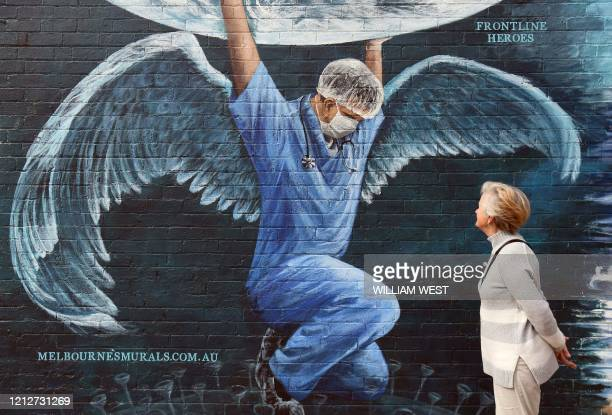 TOPSHOT A woman looks at a mural of a health worker with wings holding a globe on International Nurses Day in Melbourne on May 12 2020 As frontline...