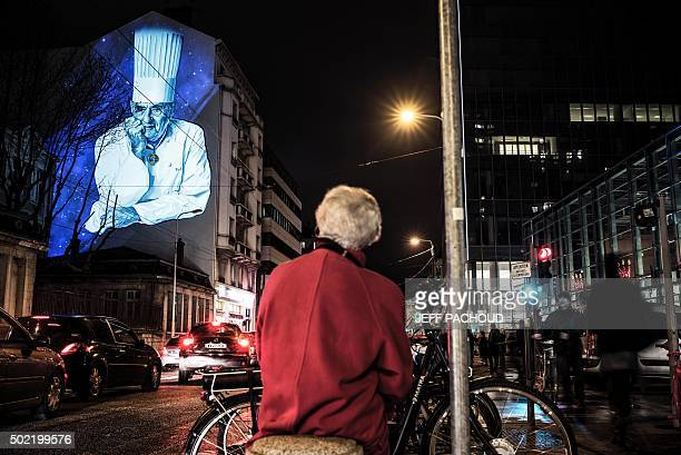A woman looks at a mural of French chef Paul Bocuse painted on the side of a building in Lyon on December 21 2015 The mural was designed by artists...