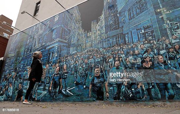 A woman looks at a mural painted by artist Logan Hicks on the HoustonBowery Wall on October 20 2016 in New York City