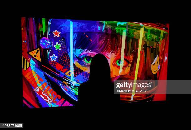 """Woman looks at a NFT by Mad Dog Jones titled """"SHIFT//"""" during a media preview on June 4 at Sotheby's for the Natively Digital: A Curated NFT Sale..."""