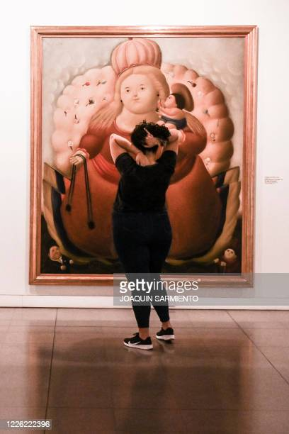 A woman looks at a painting by Colombian artist Fernando Botero at the Museum of Antioquia in Medellin Colombia amid the COVID19 novel coronavirus...