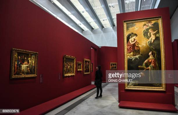 A woman looks at a painting by French painter Louis Le Nain presented during the exhibtion 'Le mystere Le Nain' at the LouvreLens in Lens northern...