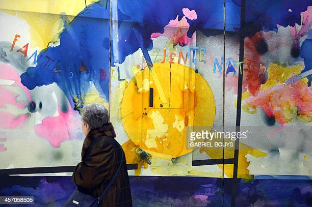 A woman looks at a painting by Italian artist Mario Schifano as she visits the exhibition Anni 70 Arte a Roma during a press preview at the Palazzo...