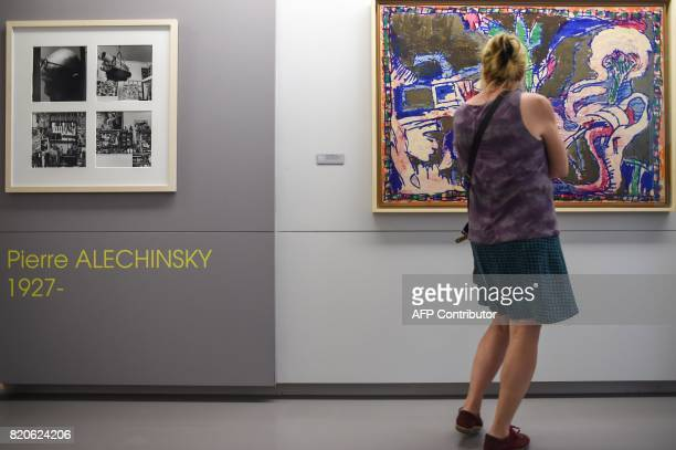 A woman looks at a painting called 'Ceci peint comme on dit dit' by Belgian artist Pierre Alechinsky during an exhibition named 'Histoires...