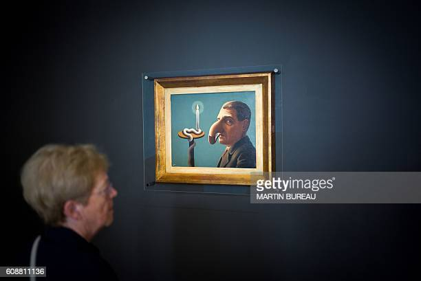 A woman looks at a painting during a visit of the exhibition of Belgian painter Rene Magritte on September 20 2016 at the Georges Pompidou museum in...