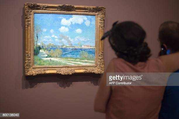 A woman looks at a painting entitled 'Bougival' by late French painter Alfred Sisley as part of the exhibition 'Sisley the impressionist' at the...