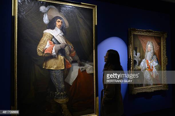 A woman looks at a painting of a musketeer next to a portrait Duke of Lauzun Antonin Nompar de Caumont displayed in the exhibiton 'Mousquetaires' in...