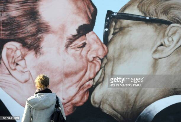 A woman looks at a painting on the so called East Side Gallery featuring the famous kiss between then Soviet leader Leonid Brezhnev and East German...