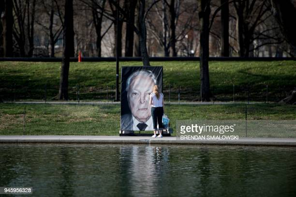 A woman looks at a portrait of a Holocaust survivor during the Lest We Forget exhibition along the Reflecting Pool at the National Mall on Holocaust...