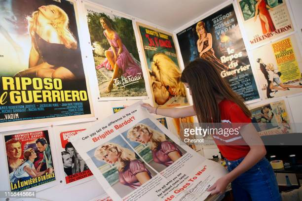 A woman looks at a poster of a movie with French actress Brigitte Bardot during the exhibition The Bardot years 19521973 at Orsay Gallery on June 12...