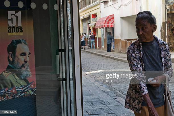 A woman looks at a poster with a portrait of Cuban leader Fidel Castro in Havana during the 51th Anniversary of the victory of the Revolution against...