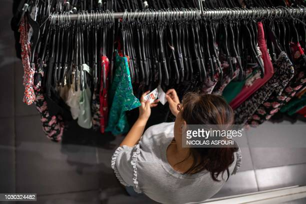 A woman looks at a price tag on a dress in a mall in Beijing on September 10 2018 China's consumer price inflation rose more than expected in August...
