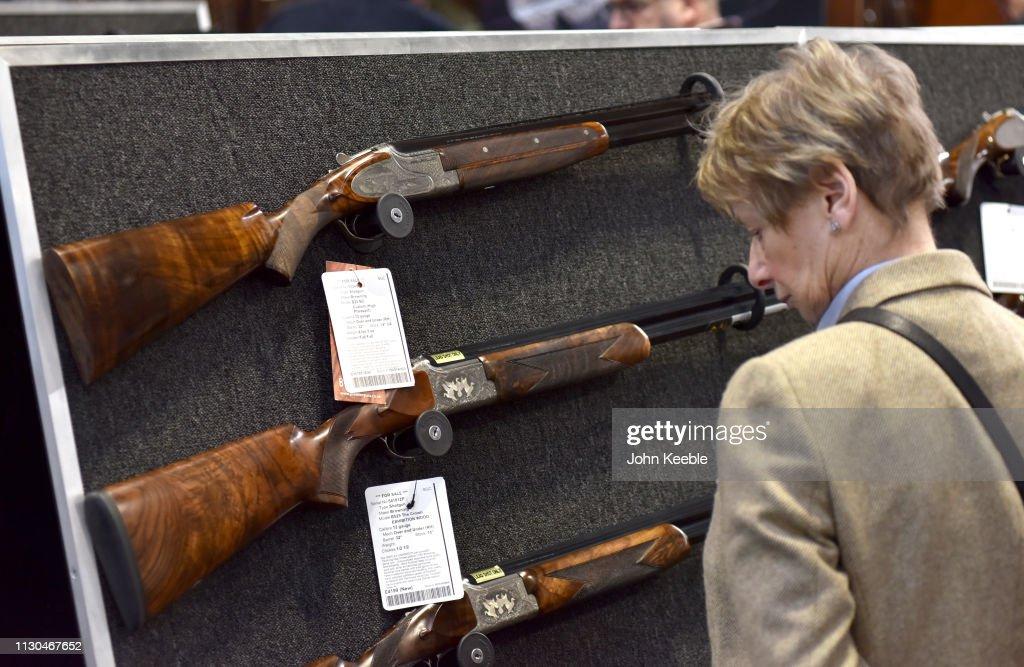 A woman looks at a range of Browning shotguns at the Great British