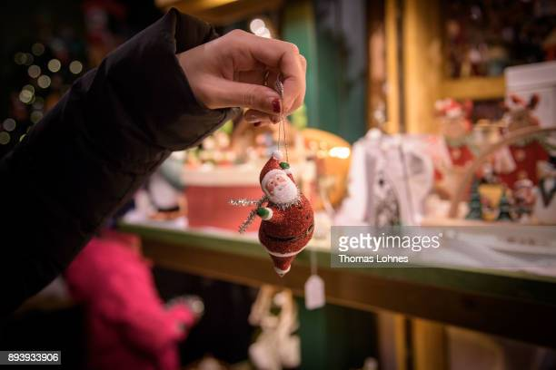 A woman looks at a Santa Claus Christmas decoration at the annual Christmas market at Roemerberg on December 16 2017 in Frankfurt Germany Christmas...