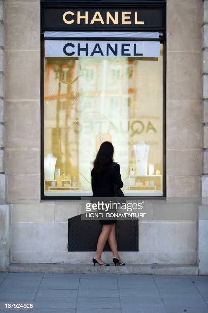 A woman looks at a shop window of a Chanel fashion store on April 26 2013 at the Place Vendome in Paris AFP PHOTO / LIONEL BONAVENTURE
