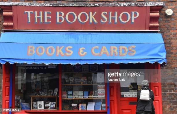 Woman looks at a sign on the door of a book shop window which is closed on November 11, 2020 in Leek, England. The Booksellers Association has called...