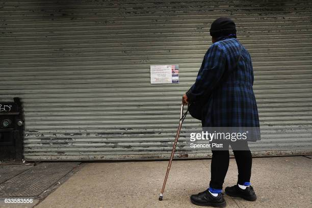 A woman looks at a sign on the gate of a closed Yemeni bodega on February 2 2017 in New York City Across the city Yemeni bodega and grocerystores...