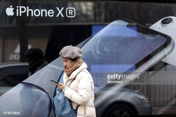 A woman looks at a smartphone while walking past an advertisement for the Apple Inc iPhone XR in Beijing China on Thursday Jan 3 2019 Applecut its...