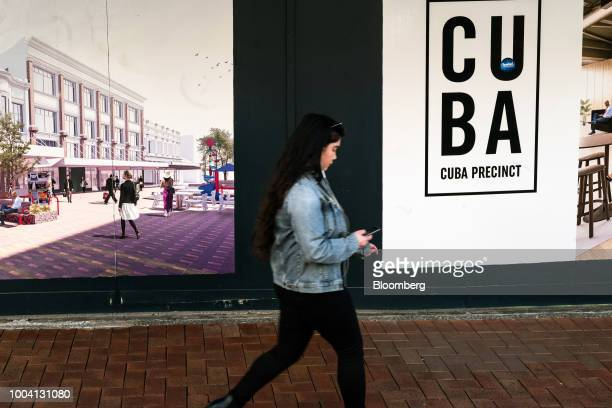 A woman looks at a smartphone while walking past an advertising hoarding on Cuba street in Wellington New Zealand on Wednesday July 18 2018 New...