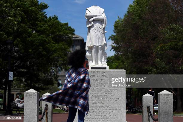 A woman looks at a statue depicting Christopher Columbus with its head removed at Christopher Columbus Waterfront Park on June 10 2020 in Boston...