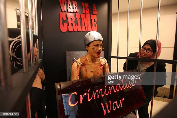 A woman looks at a statue of a torture victim on display during the Kuala Lumpur War Crimes Tribunal exhibition in Kuala Lumpur on November 18 2011...