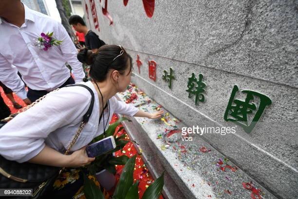 Woman looks at a stone tablet that reads blessed land for Chinese football, which is unveiled at Helong Sports Centre Stadium on June 9, 2017 in...