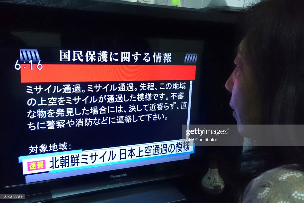 A woman looks at a television news displaying warnings via the 'J-alert' system in Tokyo on August 29, 2017, following a North Korean missile test that passed over Japan. Japanese Prime Minister Shinzo Abe said on August 29 that he and US President Donald Trump agreed to hike pressure on North Korea after it launched a ballistic missile over Japan, in Pyongyang's most serious provocation in years. / AFP PHOTO / Kazuhiro NOGI
