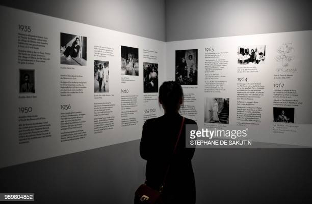 A woman looks at a timeline at the exhibition L'Alchimie Secrete d'Une Collection of late FrenchTunisian fashion designer Azzedine Alaia on July 2...