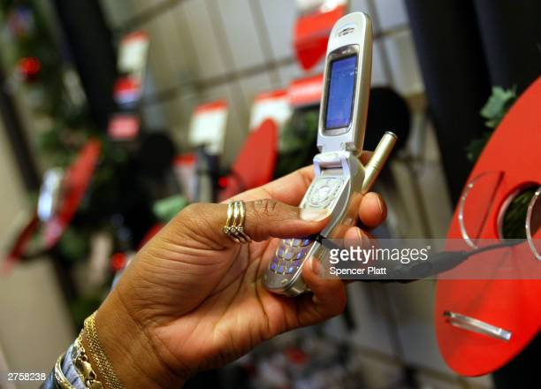 A woman looks at a Verizon cell phone November 24 2003 in New York City US cell phone customers can now switch carriers without changing phone...