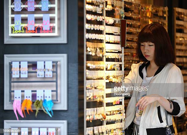 A woman looks at accessories displayed at a store in the shopping district of Harajuku in Tokyo Japan on Thursday May 30 2013 The national price...