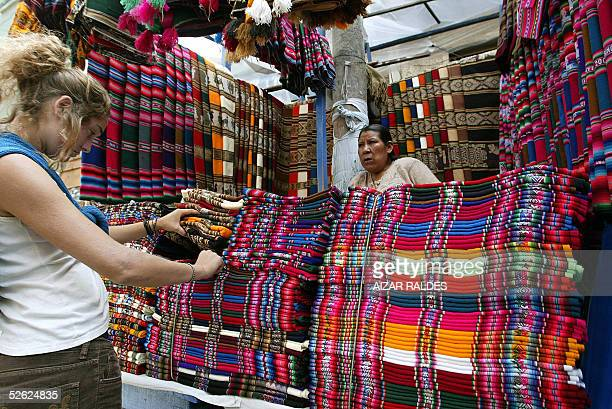 A woman looks at 'aguayos' Bolivian typical fabric in a stall in La Paz 11 March 2005 With a population of 8724156 inhabitants according to the July...