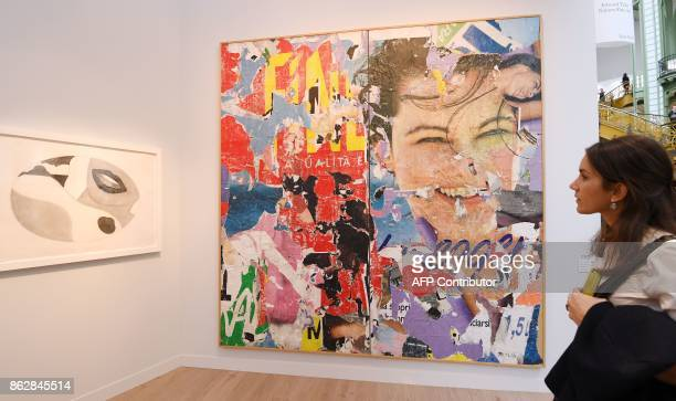 A woman looks at an artwork untitled '19591980' by Italian artist Mimmo Rotella as she visits the Paris International Contemporary Art Fair at the...