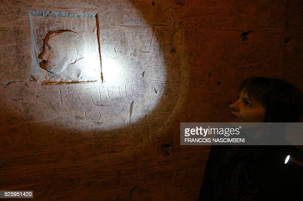 A woman looks at an engraving of Louis Pasteur in the chalk quarries used by Ruinart Champagne house in Reims eastern France on April 20 2016 Between...