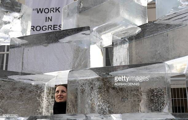"Woman looks at an ice sculpture entitled ""Work in Progress"" outside the German embassy in London, on November 9, 2009. The art installation depicts..."