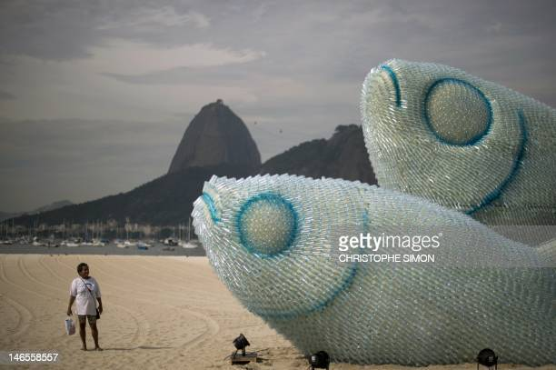 A woman looks at an installation made of recycled plastic bottles representing fishes in Botafogo beach in Rio de Janeiro on June 19 in the sidelines...