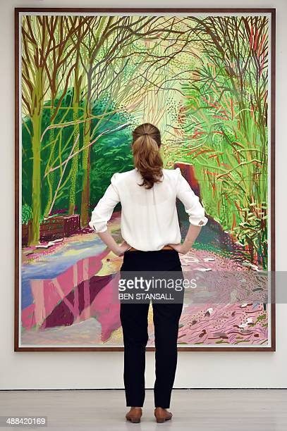 A woman looks at an iPad drawing by British artist David Hockney entitled 'The Arrival of Spring in Woldgate East Yorkshire in 2011 2 January' during...