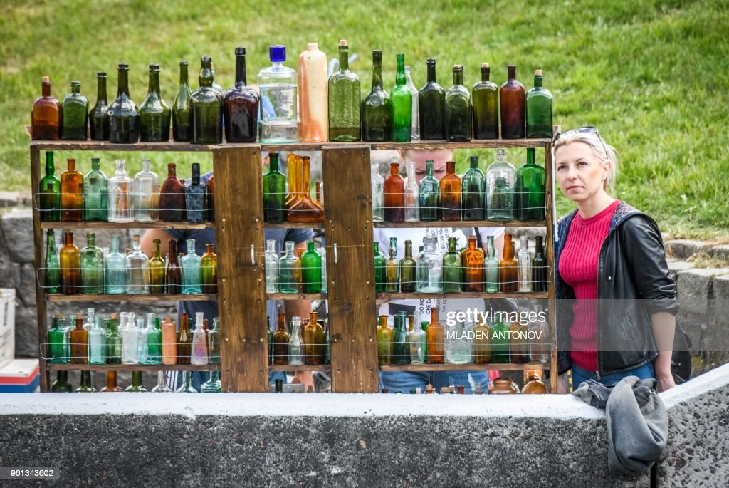 A woman looks at antiques bottles for sale in Kaliningrad on May 22 ...