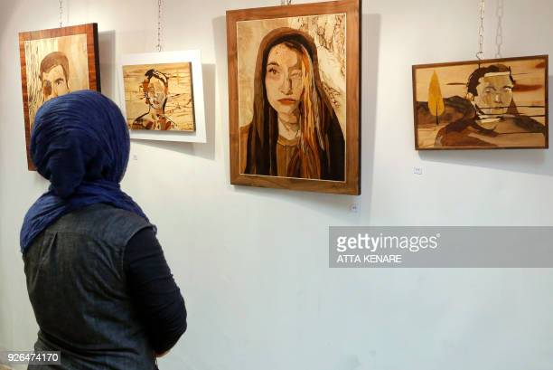 A woman looks at art work made by Iranian victims of acid attacks at the Ashianeh gallery in Tehran on February 28 2018 Acid attacks have been an...