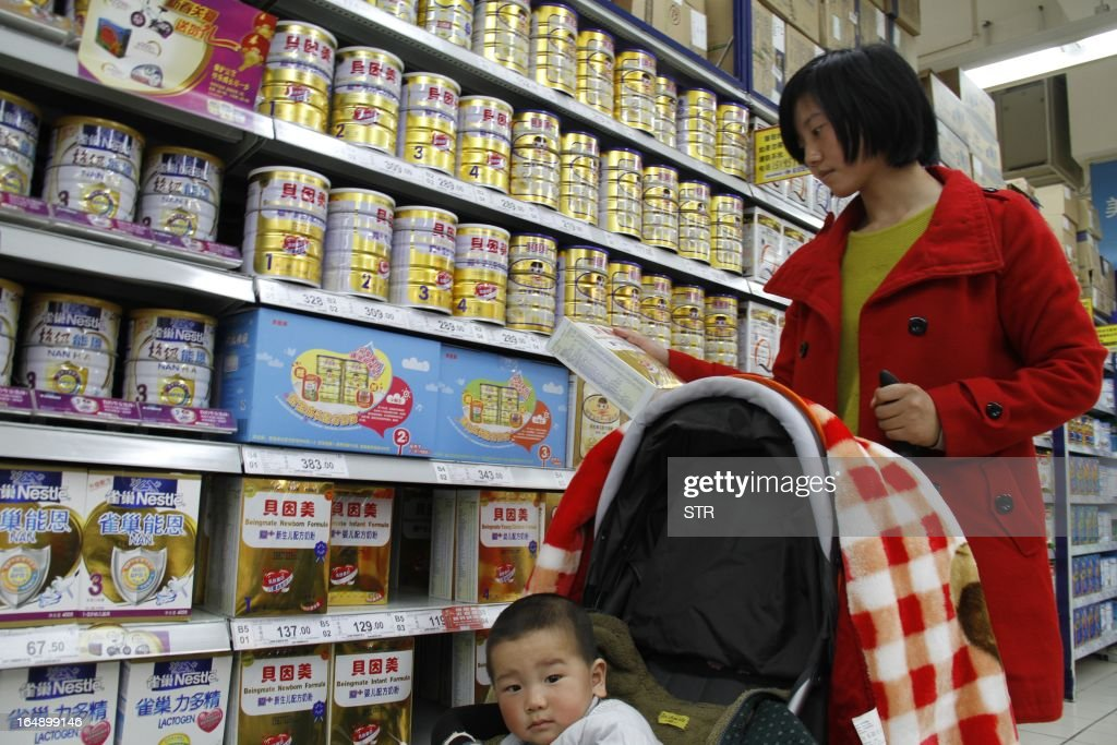 A woman looks at baby milk powder in a supermarket in Nanjing, east China's Jiangsu province on March 29, 2013. The Chinese partner of Hero Group, a major Swiss baby formula manufacturer, has been accused of deliberately mislabelling milk powder and a senior employee has been detained, officials said on March 26, 2013. CHINA