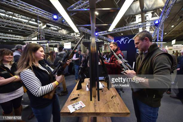 Woman looks at Blaser R8 Silence rifle while a man looks at a Blaser Professional Success rifle at the Great British Shooting Show at NEC Arena on...