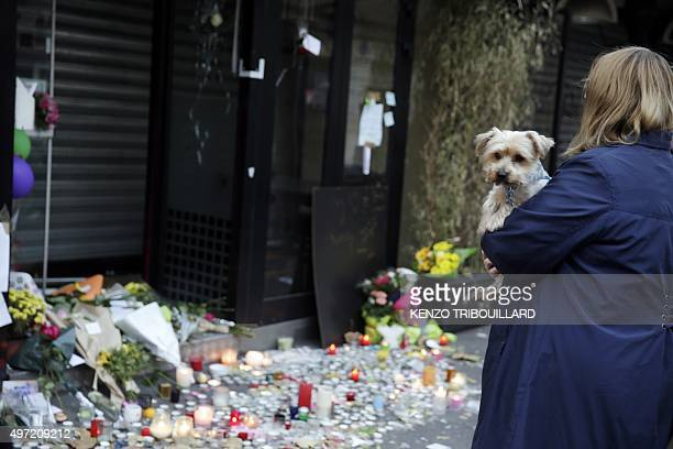 Woman looks at candles and flowers placed at the entrance of Japanese restaurant next to the cafe 'La Belle Equipe', Rue de Charonne, on November 15,...