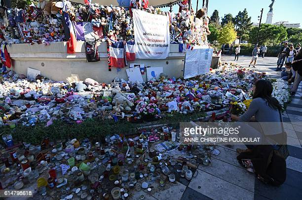 A woman looks at candles toys and flowers placed in commemoration to victims at a pavilion at the Promenade des Anglais in Nice southeastern France...