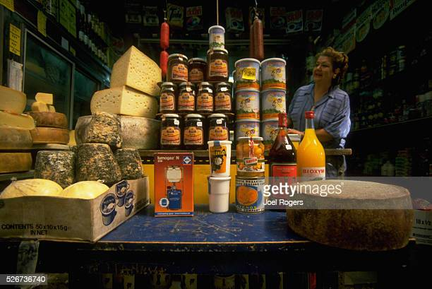 A woman looks at canned and jarred goods and wheels of cheese on display at a market stall in Rethymnon Crete Greece