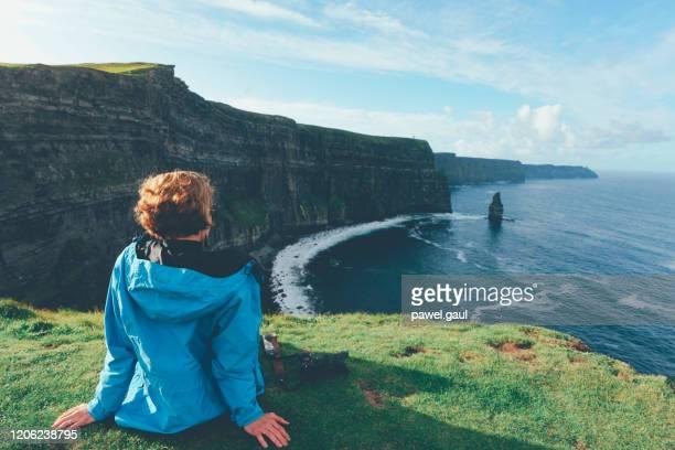 la donna guarda cliffs of moher in irlanda - irlanda foto e immagini stock
