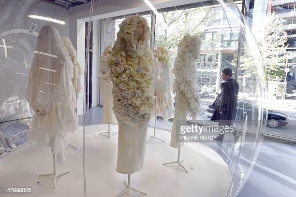 A woman looks at creations by Japanese designer Rei Kawakubo for Comme des Garçons fashion house exhibited at the Cité de la Mode on April 11 2012 in...