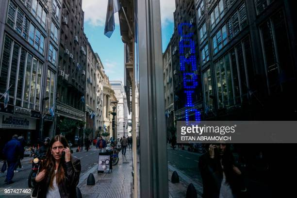 A woman looks at currency exchange values seen in the buysell board of an exchange bureau in the financial district of Buenos Aires on May 11 2018...