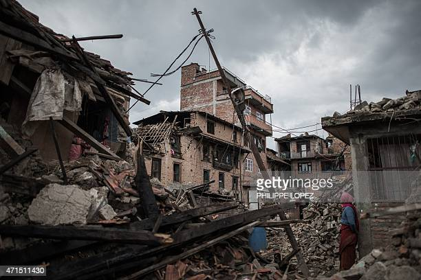 A woman looks at damaged buildings in Khokana a village dating back hundreds of years on the outskirts of Kathmandu on April 29 following a 78...