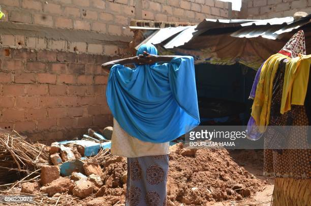 A woman looks at debris in a damaged house following heavy rains in Niamey on June 15 2017 At least nine children have been killed in Niger as heavy...