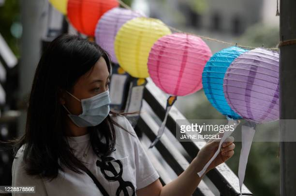 Woman looks at decorative lanterns with messages of goodwill on display for the Mid-Autumn Festival, in an area which was last year covered with...