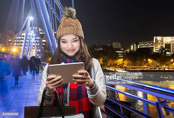 woman looks at digital tablet in urban city.